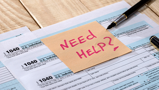 "Tax forms with ""Need Help?"" on a post-it note"