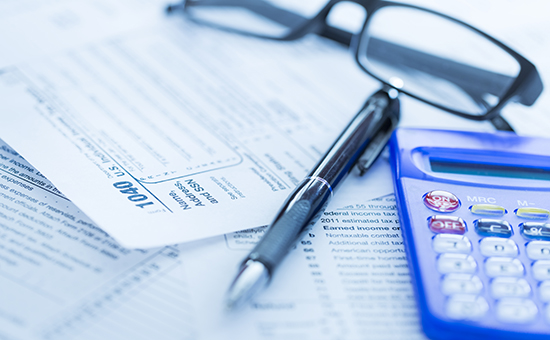 Tax forms with pen and calculator