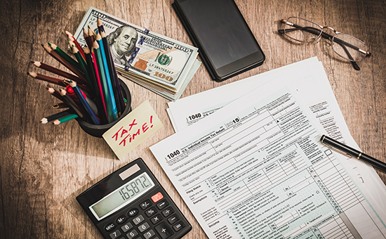 Tax forms with pens and calculator ready to do taxes